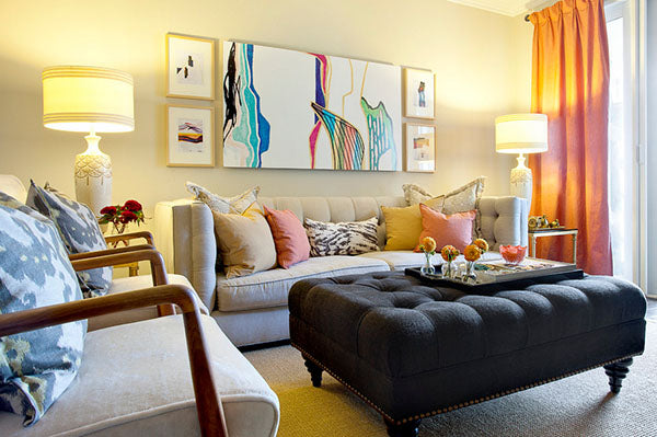 Cream living room with cream sofa, and large black pouffe coffee table