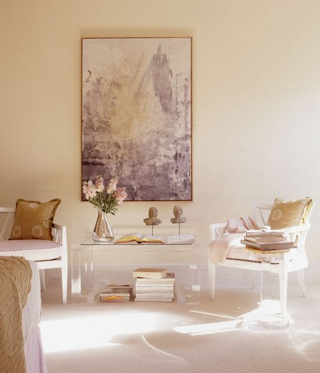 A cream living room with white wooden seats and benches, and purple and cream artwork on the wall