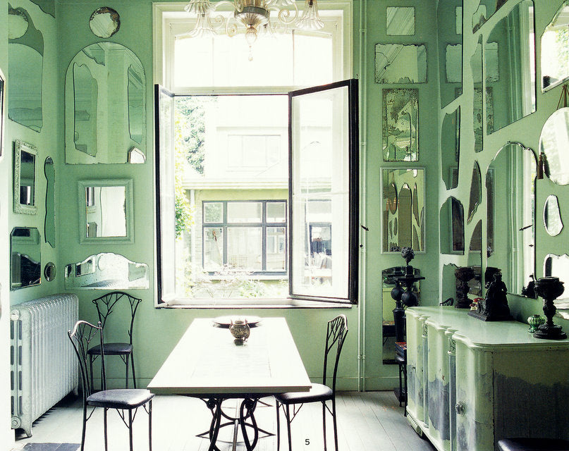Mint green dining room, with different shaped mirrors covering all of the walls