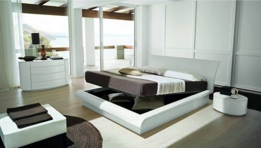 White And Brown Bedroom With Folding Bed Storage And Sliding Door To A Balcony