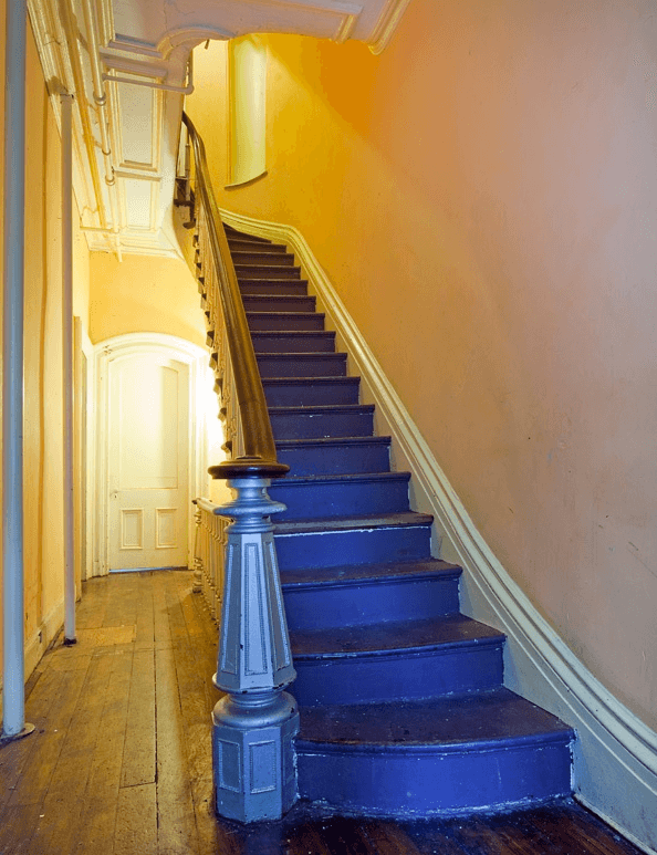 Victorian style townhouse hallway, with original features and floors, and a dark blue painted staircase