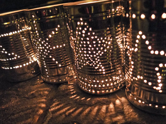 Star Patterns Pierced Onto Old Food Cans With A Lit Candle Inside Them