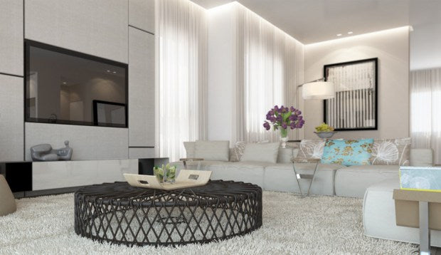 Round woven coffee table on a white rug, with white corner sofa in a white living room