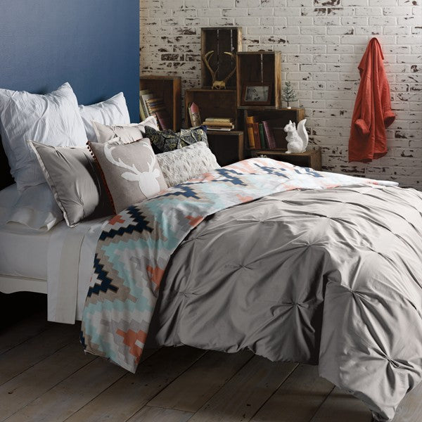 Dark blue and white industrial style bedroom, with grey bedding and lots of cushions