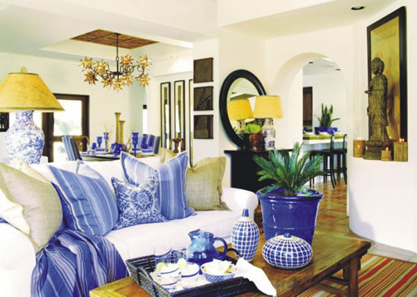 Modern and stylish white living room with a number of blue accessories throughout, including cushions, lamps and planters