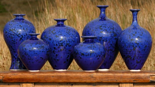 Six dark blue vases and jars on a wooden unit