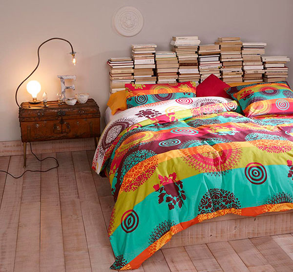 Stacked books behind a bed used as a headboard