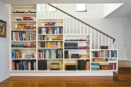 Tiered white shelving stood against the side of a staircase
