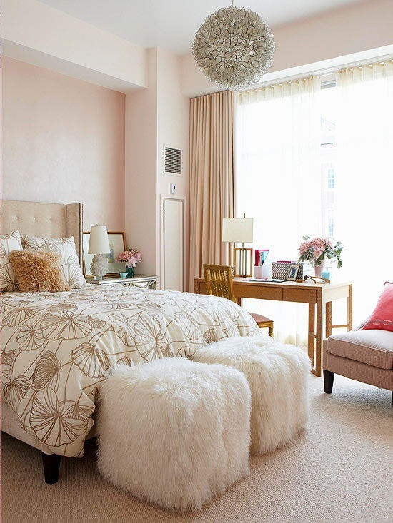 A cream and beige bedroom with cream curtains, white bedding and a wooden desk by the side of the bed in front of the window