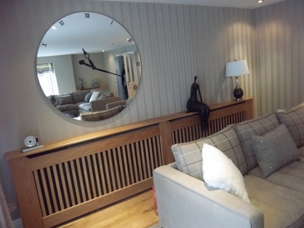 A large round mirrored wall clock on a living room wall
