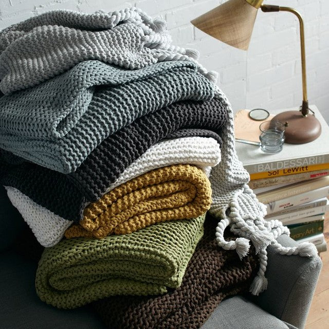 A pile of different coloured throws on an armchair