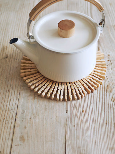 Wooden clothes pegs used as a coaster for a metal tea pot