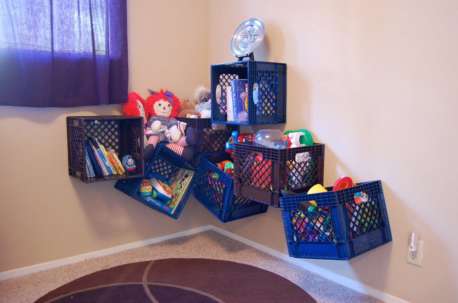 Blue plastic crates attached to the wall with toys and books in them