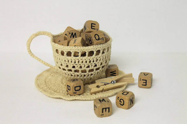 A novelty knitted teacup containing wooden letter blocks