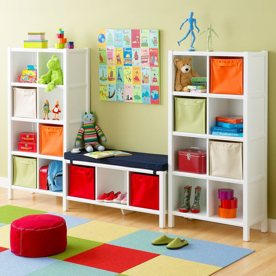 Light green kids bedroom with lots of white storage shelves, containing toys and containers