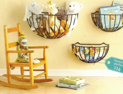 Toys and childrens books in black baskets hung on the wall