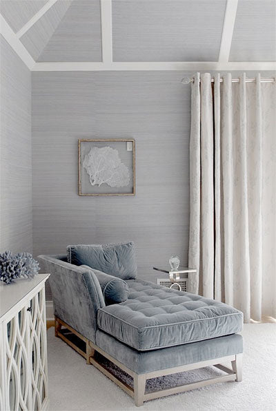 Plain grey wallpaper in a living space with matching ceiling, with dusty blue chaise long type chair