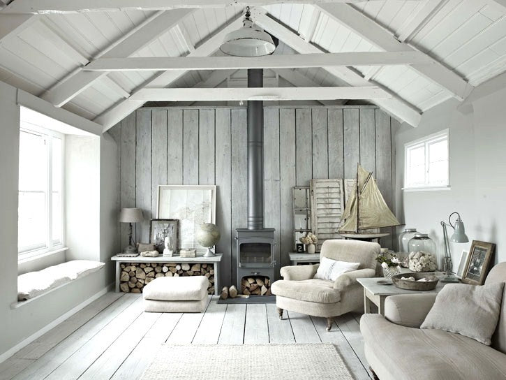 Industrial style loft space with grey wooden panels on the walls and floor and white wooden panels on the ceiling