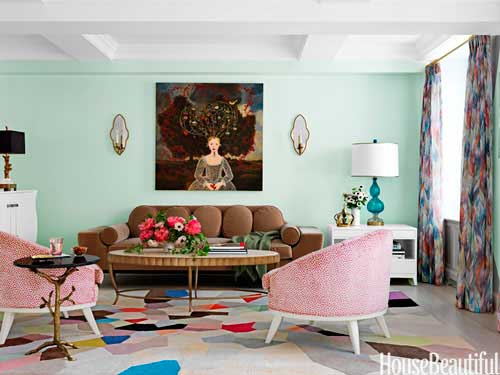 Mint green living space with pink armchairs and brown sofa