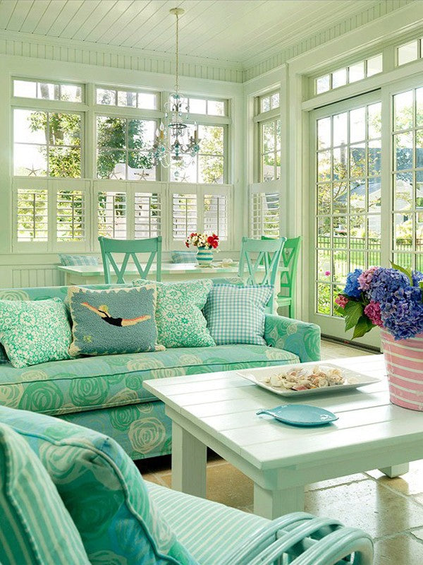 Light green wooden conservatory with window shutters and turquoise sofa, chair and dining table
