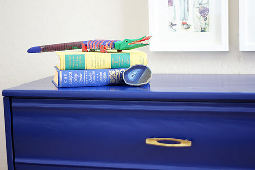 Set of drawers in dark blue, with two books on top and a toy crocodile