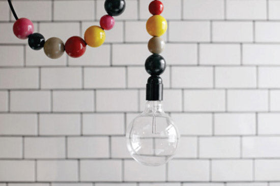 A light bulb hanging from a beaded electricity cord