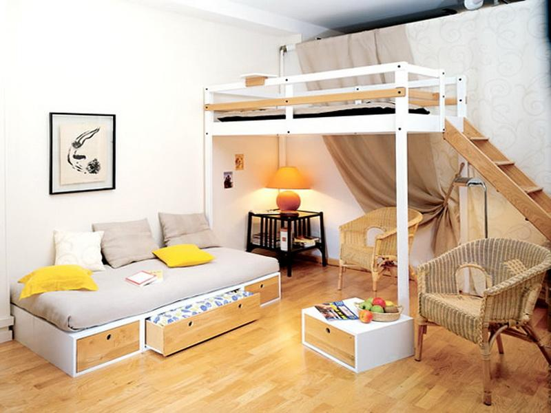 White bunk bed with seat and table underneath, and to the right of it a day bed with grey bedding and yellow cushions