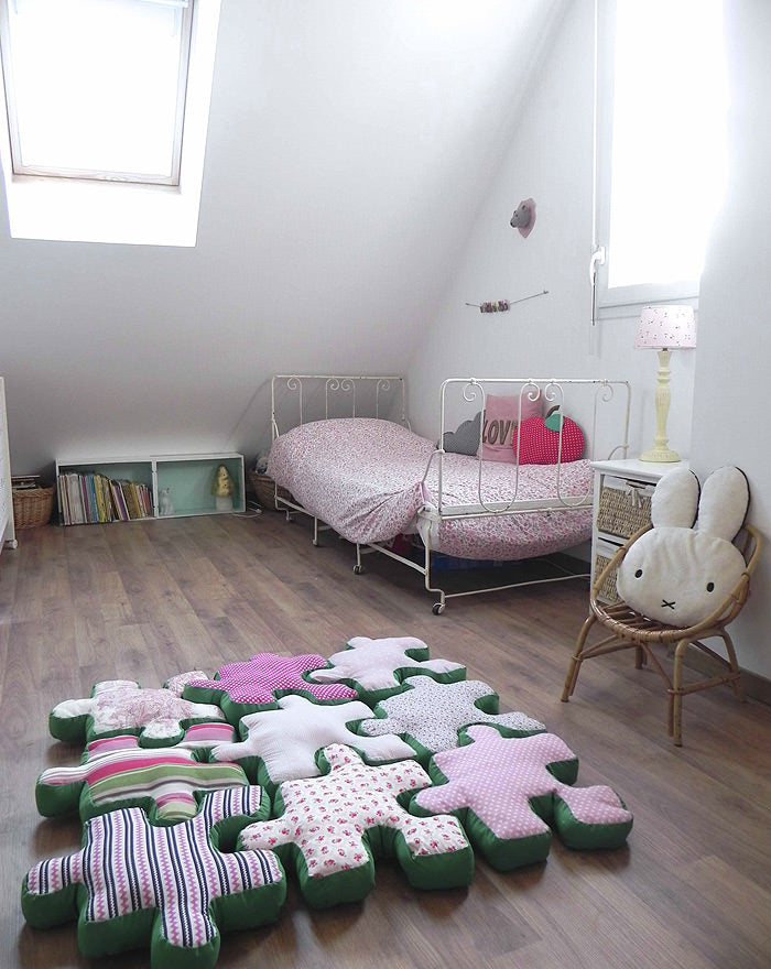 Childrens loft bedroom with green, white and pink cushions on the floor shaped like jigsaw pieces