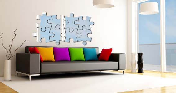 Heavily photoshopped image of a puzzle mirror hung above a black leather sofa