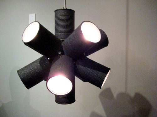 Eight Black Cans Arranged Like Lines Dissecting A Centre Point, In Order To Create A Funky Lampshade