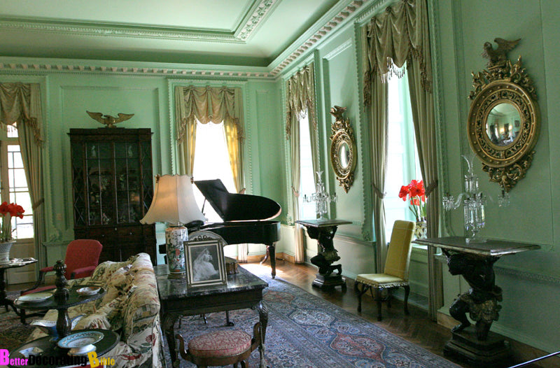 Traditional mint green living space, with ornate and intricate ceiling mouldings and black grand piano in the corner