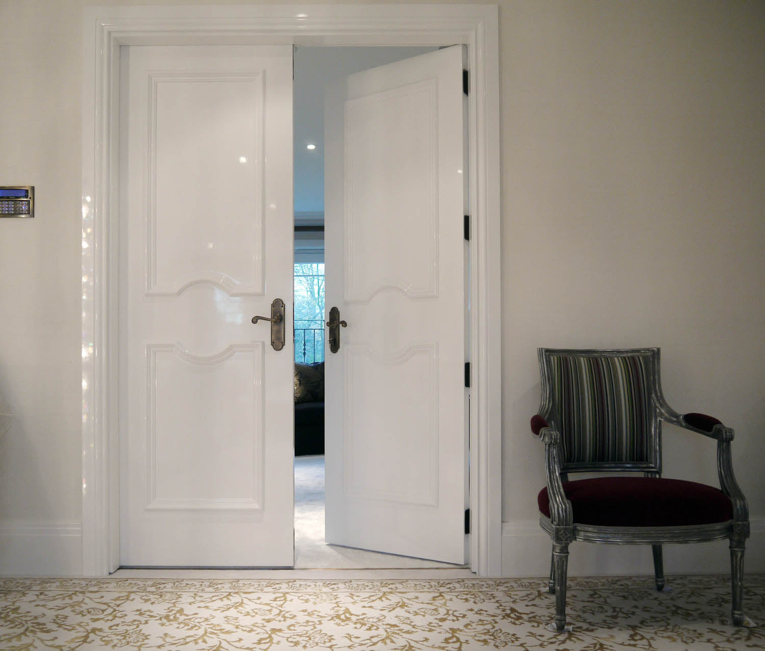 White double doors slightly open, looking into a living room