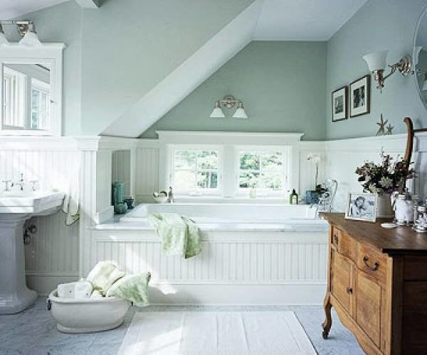 Light mint green bathroom walls, with white wall panels, tub and sink