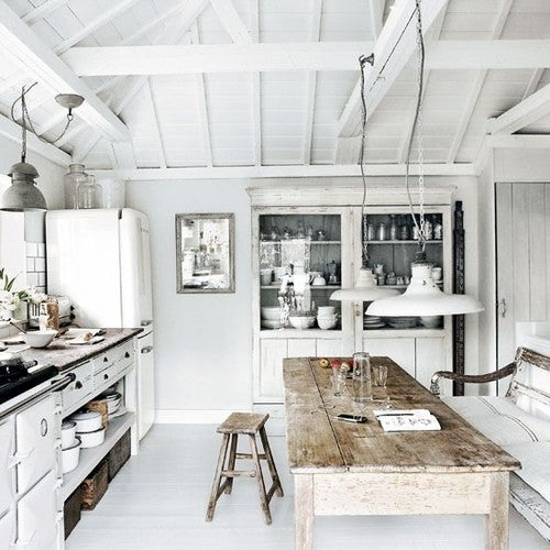 Rustic farmhouse style kitchen in white, with distressed wooden table