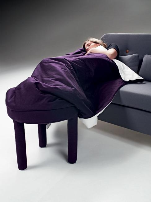 A person sat on a dark blue sofa with feet up on stool, covered in a purple blanket