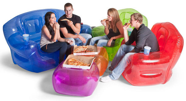 Four people eating pizza, while sitting on coloured inflatable furniture