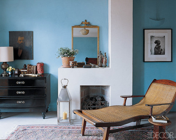 Light blue and white living room, with white fireplace surround and wooden chaise lounge style chair