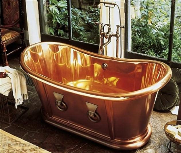 Old fashioned copper bathtub with ornate tap and fixings