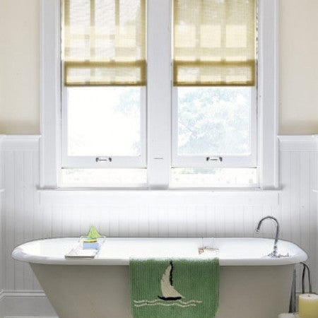 White and cream bathroom with beige roman blinds at the windows, above a bathtub