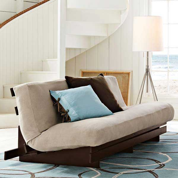 Brown and beige futon in a white beach hut style living space, by the sea