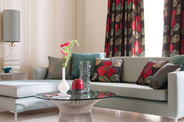 Brown, red and beige curtains and matching cushions on a corner sofa
