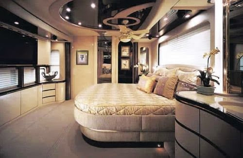 Large camper van bedroom with luxury cream bed and extravagant finish