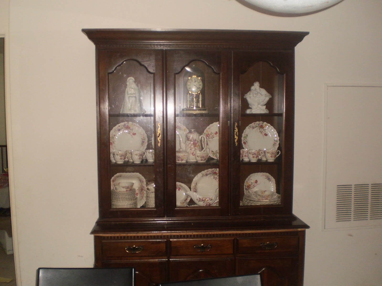 A dark wood plate cabinet and drawers