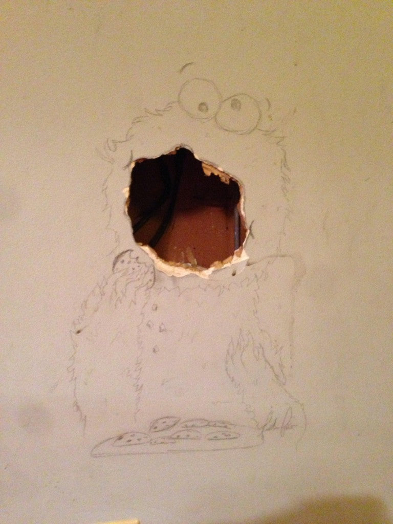 A hole in the wall turned into the mouth of the cookie monster using a pencil drawing