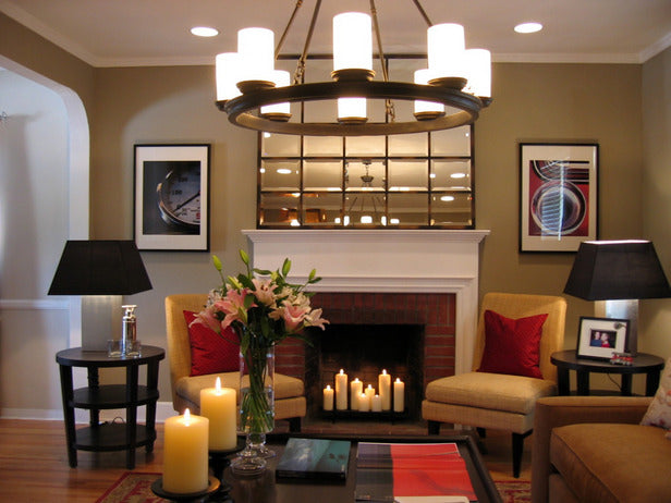Cosy living room with beige, cream and brown interior and lit candles in the brick framed fireplace