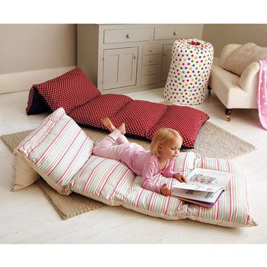 Fold out cream and pink striped day bed, with a little girl reading a book on it