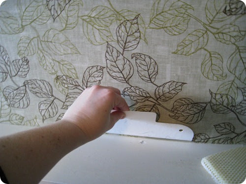 A Person Holding A Finishing Tool Against A Leaf Pattern Wallpaper
