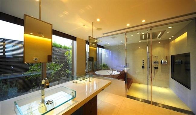 Cream and beige large bathroom with massive shower cubicle with full glass wall