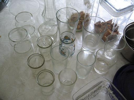A number of glasses and jars on a kitchen counter top