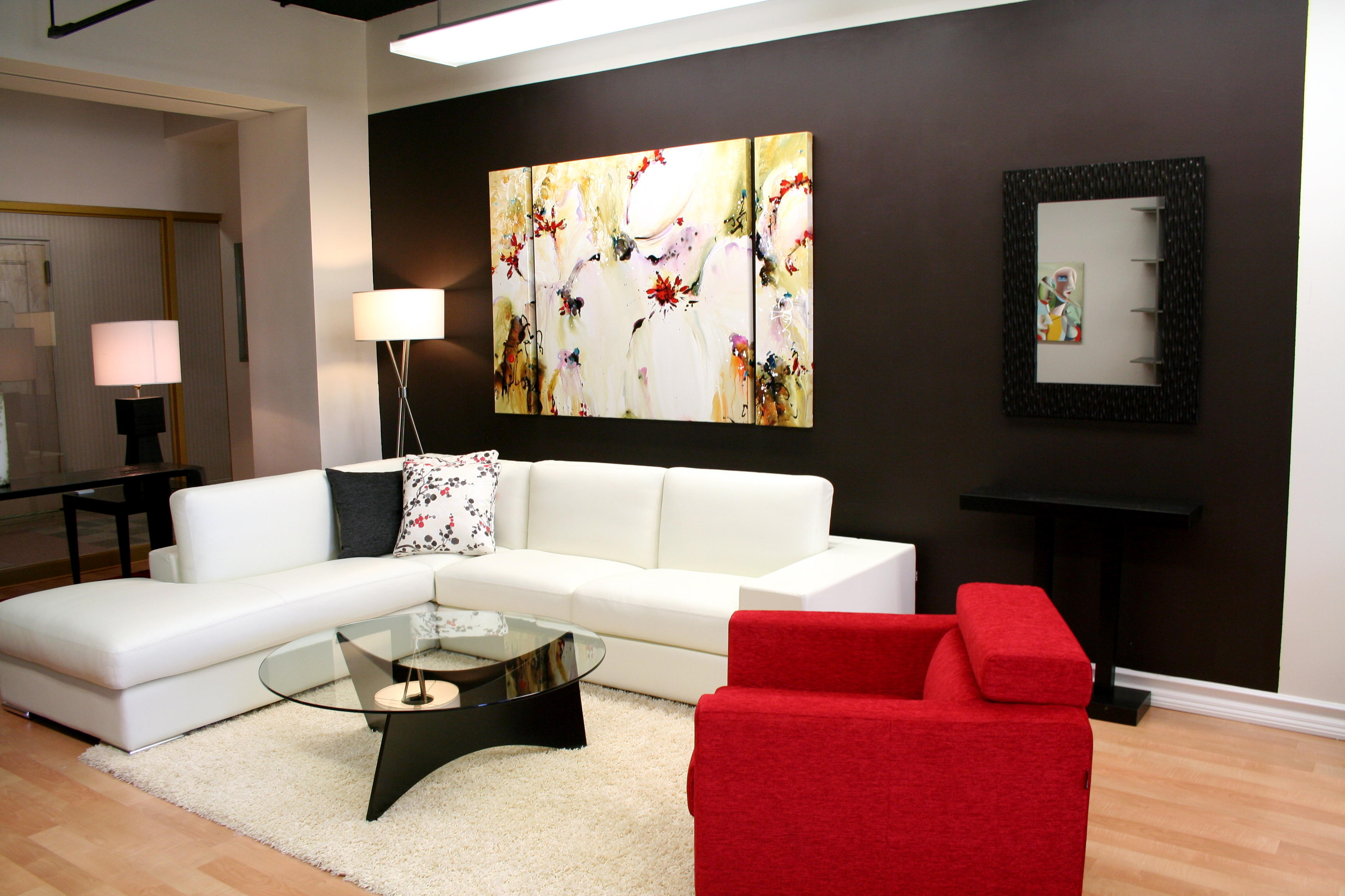Brown and cream living room, with white corner sofa and red armchair
